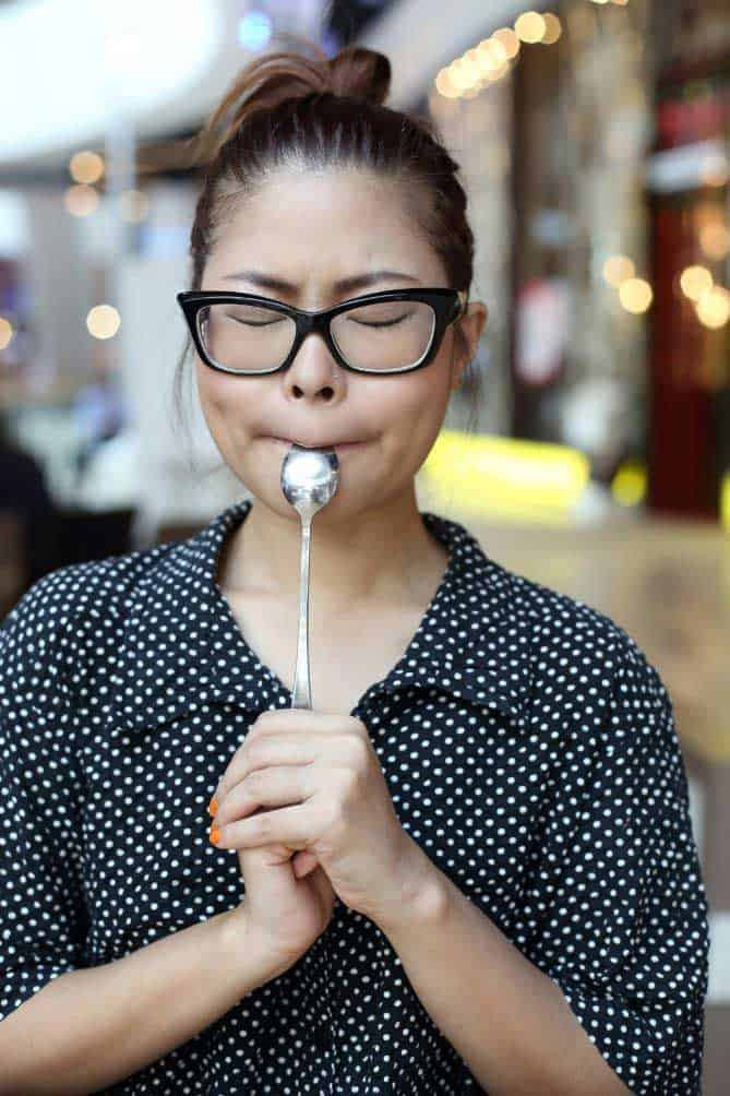 Woman with spoon in mouth tasting for flavor. | MakeSauerkraut.com