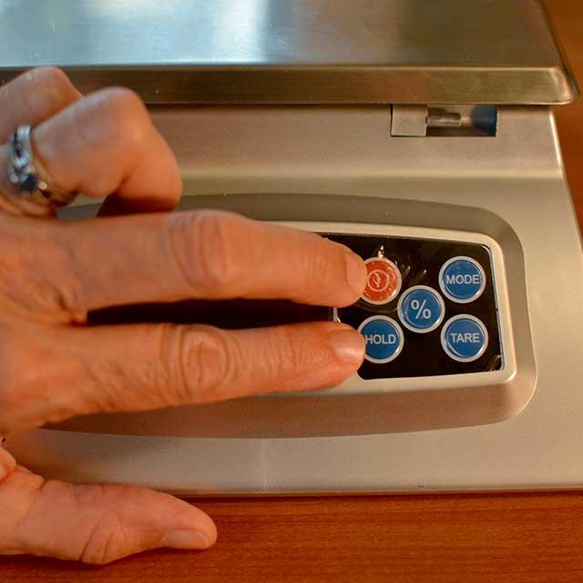 Fingers reaching to press buttons on the MyWeigh KD-8000 digital scale. | MakeSauerkraut.com
