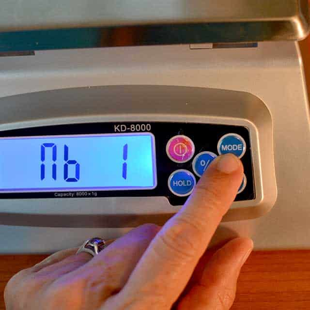 "Fingers reaching to press ""mode"" on the MyWeigh KD-8000 digital scale. | MakeSauerkraut.com"