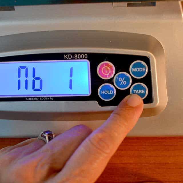 "Fingers reaching to press ""tare"" on the MyWeigh KD-8000 digital scale. | MakeSauerkraut.com"