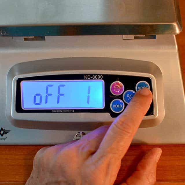 """Fingers reaching to press """"mode"""" on the MyWeigh KD-8000 digital scale with monitor showing """"off 1"""". 