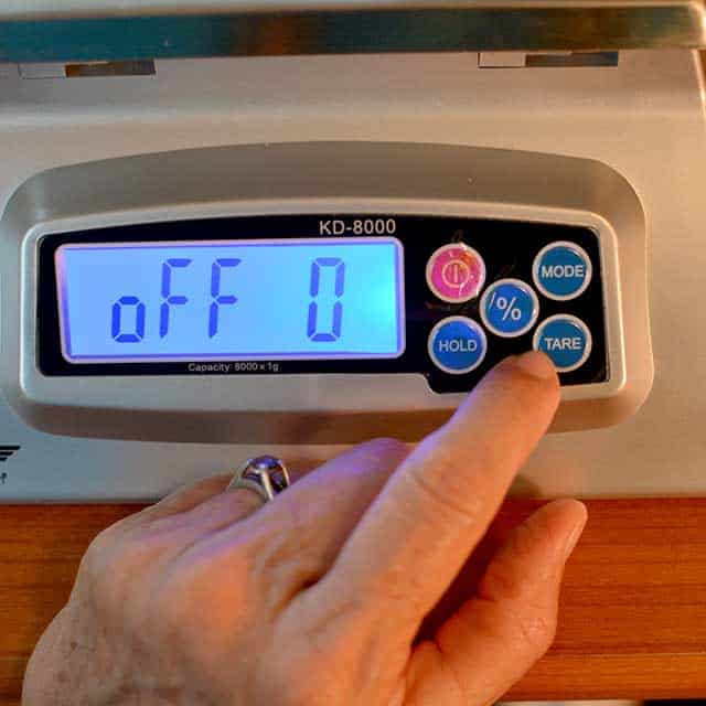 """Fingers reaching to press """"tare"""" on the MyWeigh KD-8000 digital scale with monitor showing """"off 0"""". 