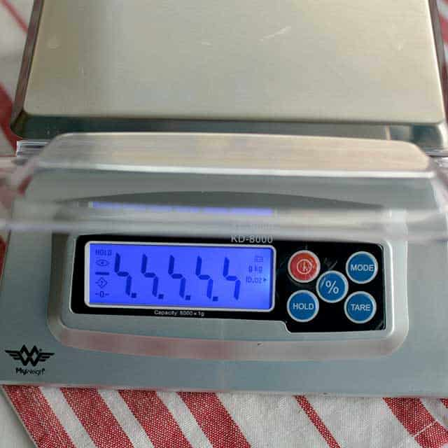 """Front view of MyWeigh KD-8000 digital scale on striped red and white cloth and monitor showing """"99999"""". 