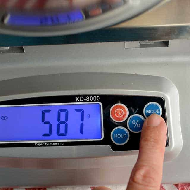 """Fingers pressing """"mode"""" on MyWeigh KD-8000 digital scale and the screen showing """"587"""". 