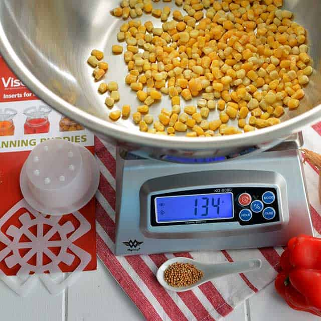 """Metal bowl with corn kernels on top of the MyWeigh KD-8000, white spoon with herbs, fermentation weight and the monitor showing """"134"""". 