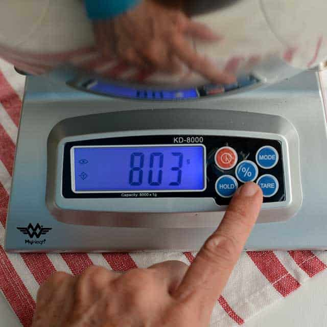 """Fingers pressing """"%"""" on MyWeigh KD-8000 digital scale and the screen showing """"803"""". 