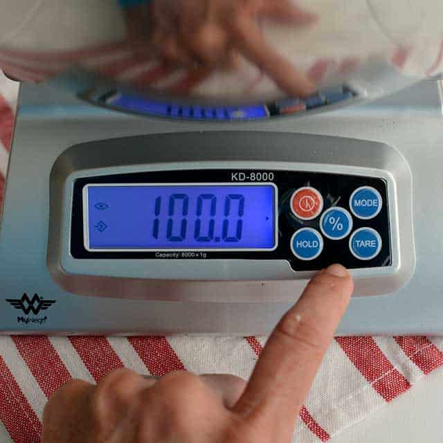 """Fingers pressing buttons on MyWeigh KD-8000 digital scale and the screen showing """"100.0"""". 