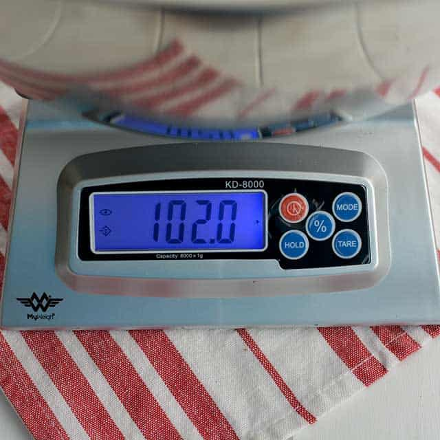 """Front view of MyWeigh KD-8000 digital scale and the screen showing """"102.0"""". 