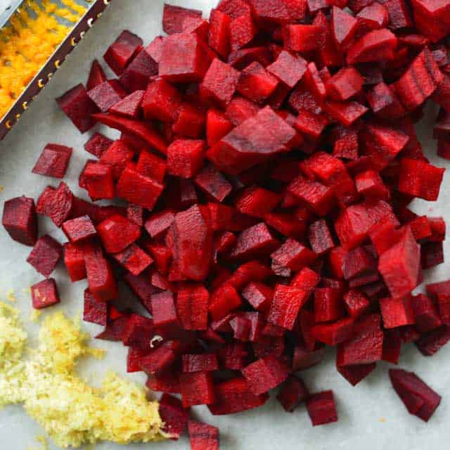 Pile of diced red beets with grated ginger on the bottom left of the picture. | MakeSauerkraut.com