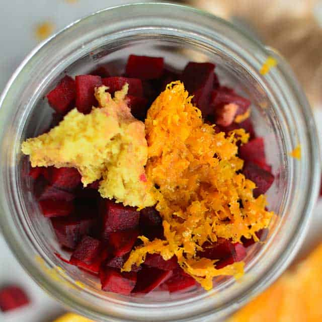 Top view of diced red beets and grated ginger on top inside a jar. | MakeSauerkraut.com