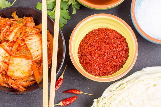 A bowl of Korean chili powder alongside a serving of kimchi. | MakeSauerkraut.com