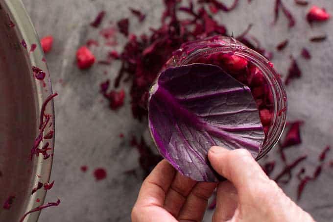 Adding floaties trap to Ruby-Red Red-Cabbage Sauerkraut. | makesauerkraut.com
