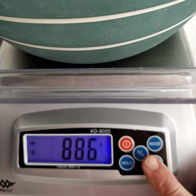 """Front view of the MyWeigh KD8000 Digital Scale with the monitor showing """"886"""" and a finger pressing a button in the scale. 