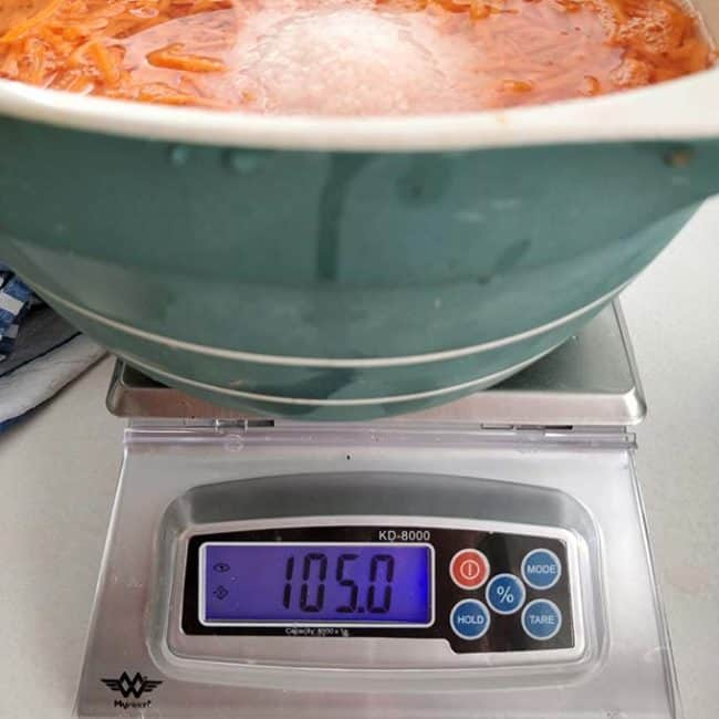 """Front view of the MyWeigh KD8000 Digital Scale with the monitor showing """"105.0"""" and partial view of a large bowl. 