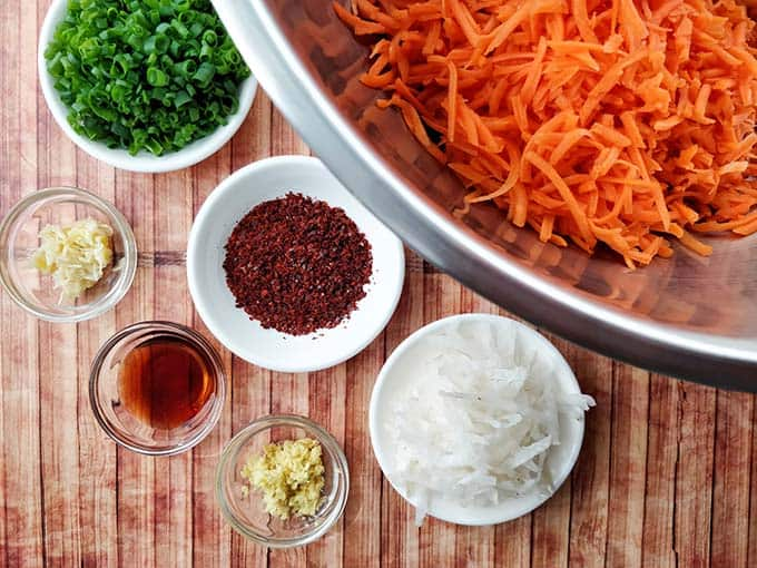 Carrot Kimchi ingredients prepped and ready for mixing with piles of grated carrots inside a big metal bowl and herbs and spices in small and white bowls. | MakeSauerkraut.com
