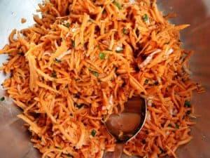 Carrot Kimchi seasonings mixed into shredded, brined, and drained carrots. | Makesauerkraut.com