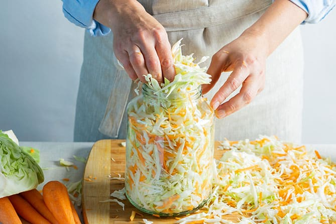 Woman packing a jar with sliced cabbage and grated carrot mixture for making sauerkraut.