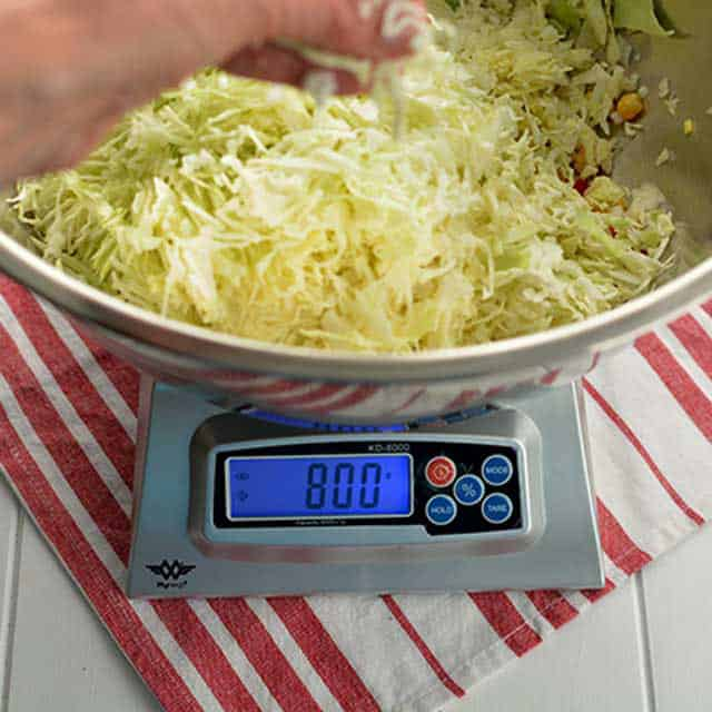 Hand adding sliced cabbage to metal bowl on My-Weigh KD-8000 scale. | Makesauerkraut.com