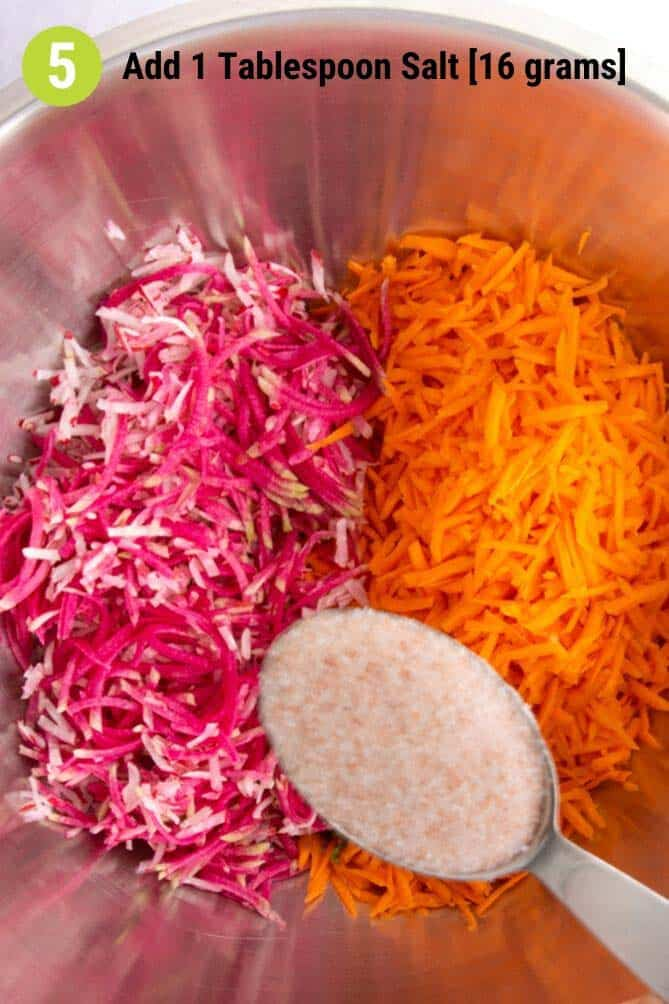 Tablespoon of salt ready to add to bowl of grated radish and carrots. | MakeSauerkraut.com