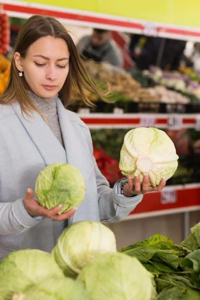 Woman in store holding a head a cabbage in each hand. | MakeSauerkraut.com