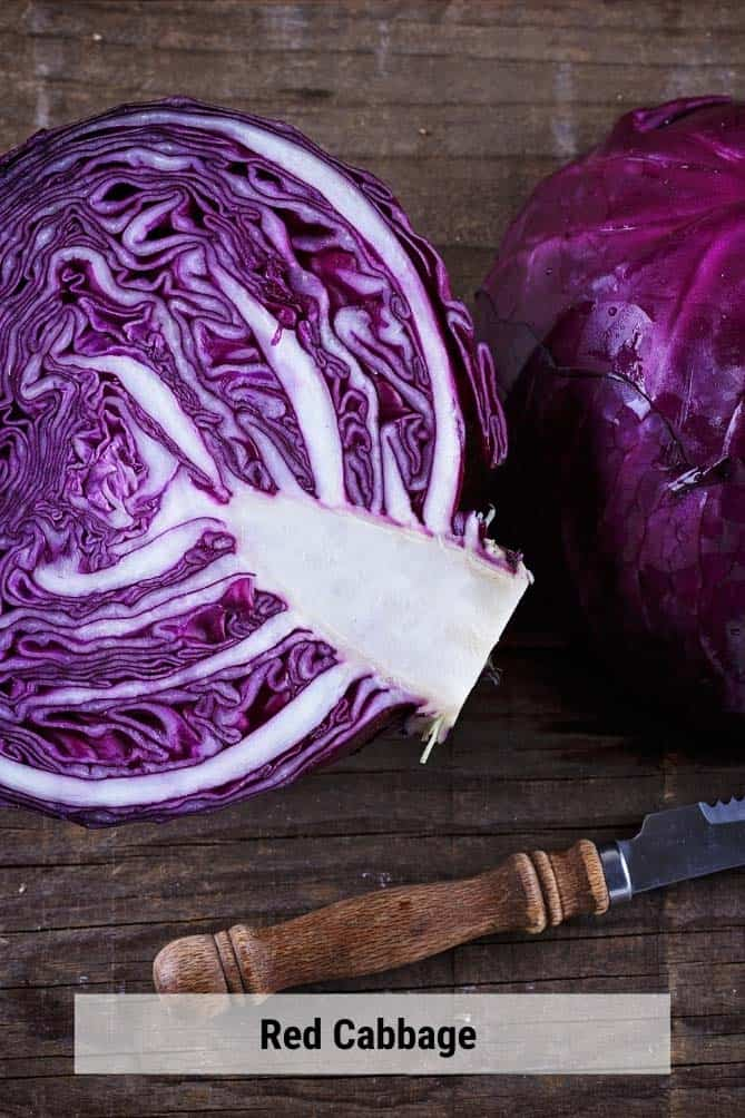 Cut half of red cabbage on a cutting board with a knife. | MakeSauerkraut.com
