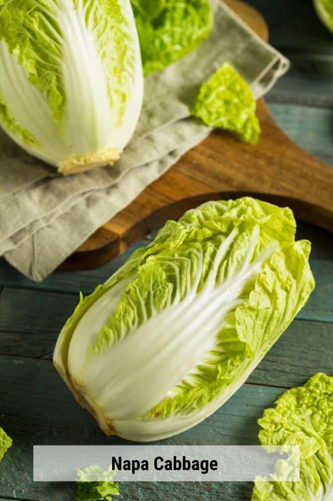 Heads of Napa cabbage on cloth napkin and cutting board. | MakeSauerkraut.com