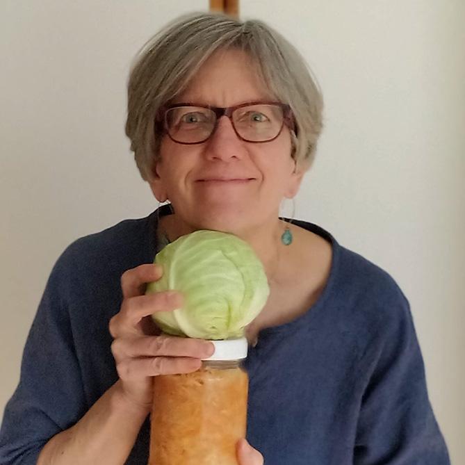 Holly Howe with a cabbage and a jar of sauerkraut. | MakeSauerkraut.com